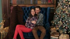 Paar sitzt das Umarmen auf einem Sofa nahe Weihnachtsbaum stock footage