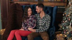 Paar sitzt das Umarmen auf einem Sofa nahe Weihnachtsbaum stock video footage