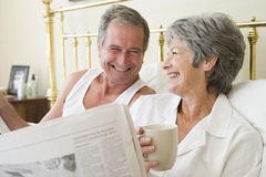 Paar in slaapkamer met koffie en kranten Stock Foto's
