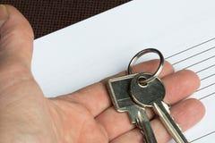 Paar sleutels in een hand met een leeg document Royalty-vrije Stock Afbeelding