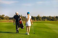Paar speelgolf op een golfcursus die aan het volgende gat lopen Royalty-vrije Stock Afbeeldingen