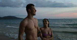 Paar Spreken die op de Handen van de Strandholding na de Zonsondergang Gelukkige Mens en Vrouw samen op Kust tijdens Vakantie lop stock footage