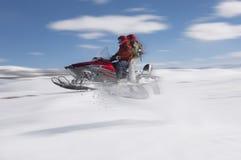 Paar-springendes Schneemobil fahrung im Schnee Stockfoto