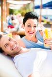 Paar in strandbar het ontspannen met dranken stock afbeeldingen