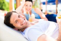 Paar in strandbar het ontspannen met dranken royalty-vrije stock foto