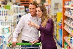 Paar in supermarkt met boodschappenwagentje Stock Foto's