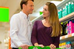 Paar in supermarkt met boodschappenwagentje Stock Foto