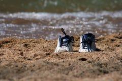 Paar tennisschoenen op strand Stock Afbeeldingen