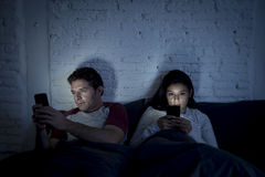 Paar thuis in bed laat bij nacht die mobiele telefoon in verhoudings communicatie probleem met behulp van royalty-vrije stock fotografie
