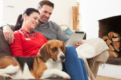 Paar thuis met Huisdierenhond die Digitale Tablet bekijken royalty-vrije stock fotografie