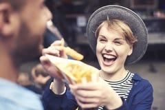 Paar tijdens het het eten straatvoedsel stock afbeelding