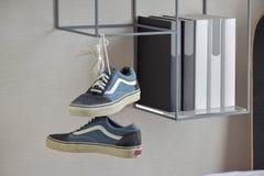 Paar toevallige blauwe tennisschoenschoenen die op boekenplank hangen Stock Fotografie