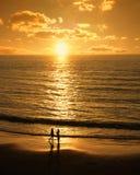 Paar trifft sich auf dem Strand bei Sonnenuntergang Stockfotografie