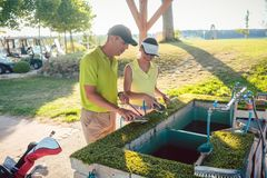 Paar of twee beste vrienden die hun clubs in een professionele golfclub schoonmaken Stock Afbeelding