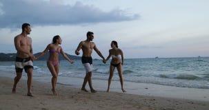 Paar twee die op Strand bij Zonsondergang Sprekend, Vrolijke Mannen lopen en Vrouwen samen bij de Mededeling van Kusttoeristen stock footage