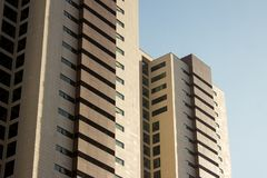 Paar tweelingbureauhigh-rise gebouwen met een gele en bruine façade royalty-vrije stock foto's