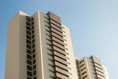 Paar tweelingbureauhigh-rise gebouwen met een gele en bruine façade stock fotografie