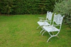 Paar uitstekende stoelen van het stijl witte gekleurde smeedijzer in de trillende groene tuin royalty-vrije stock foto's