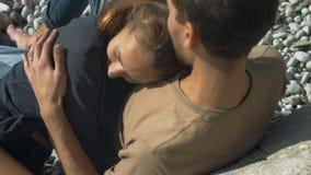 Paar umarmt das Sitzen auf dem Strand stock video