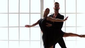 Paar van balletdansers die in zwarte kostuums dansen stock videobeelden