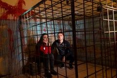 Paar van bange Halloween-slachtoffers die in wi van een metaalkooi worden gevangengenomen stock fotografie