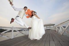 Paar van bruidegom en bruid die in huwelijkskostuum met blije em springen Stock Afbeelding