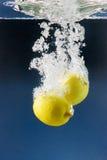 Paar van citroenen die in blauw water worden geworpen stock foto