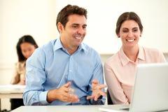 Paar van collega's die bij laptop en het glimlachen werken stock afbeelding