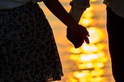 Paar van de hand van de minnaarholding met zonsopgang Royalty-vrije Stock Afbeelding