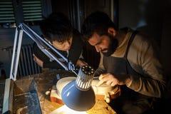 Paar van de maker van de vakliedenviool terwijl het werken aan een nieuwe viool stock fotografie