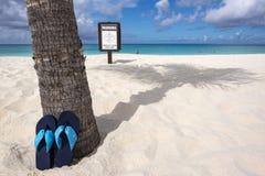 Paar van Flip Flops Leaning Against een Palm en een Waarschuwingsbord op een Strand royalty-vrije stock afbeeldingen