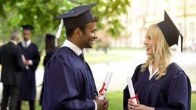 Paar van gediplomeerde studenten met diploma's die en aan elkaar spreken glimlachen stock fotografie