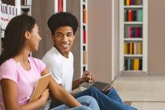 Paar van gelukkige zwarte studenten met laptop voorzien van een netwerk in bibliotheek stock fotografie