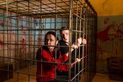 Paar van Halloween-slachtoffers in een metaalkooi worden gevangengenomen die o dat kijken royalty-vrije stock foto