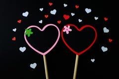 Paar van het kleine die bord van de hartvorm door wit en rood document hart op zwarte achtergrond wordt omringd Royalty-vrije Stock Foto's