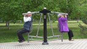 Paar van hogere opleiding bij gymnastiekmachine in groene springpark, erderly gezonde levensstijl stock footage