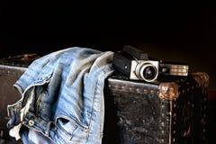 Paar van jeans en filmcamera op koffer Stock Afbeeldingen