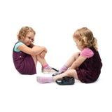 Paar van jonge meisjes die over geïsoleerde witte achtergrond zitten Royalty-vrije Stock Foto