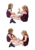 Paar van jonge meisjes die over geïsoleerde witte achtergrond zitten Stock Fotografie