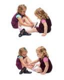 Paar van jonge meisjes die over geïsoleerde witte achtergrond zitten Stock Foto