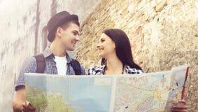 Paar van jonge reizigers met kaart: het lopen rond stad Stock Fotografie