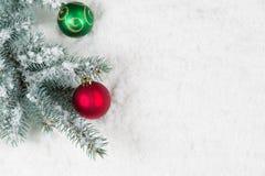 Paar van Kerstmisornamenten die van omringde Pijnboomboom hangen Royalty-vrije Stock Afbeelding