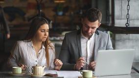 Paar van medewerkers die het werkproject bespreken terwijl het zitten bij koffie die op lunch wachten stock videobeelden