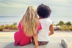Paar van meisjes die op een bank zitten Stock Foto's