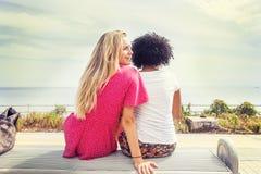 Paar van meisjes die op een bank zitten Royalty-vrije Stock Foto