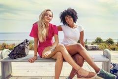 Paar van meisjes die op een bank zitten Royalty-vrije Stock Afbeeldingen
