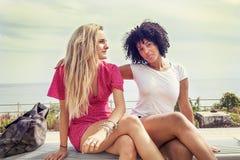 Paar van meisjes die op een bank zitten Stock Afbeelding