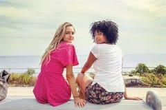 Paar van meisjes die op een bank zitten Stock Afbeeldingen