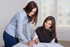 Paar van meisjes in formele kleding die bedrijfsdocumenten ondertekenen Royalty-vrije Stock Foto's