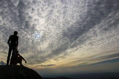 Paar van mensen die op de zonsondergang op een heuvel letten dichtbij Gouden rots, royalty-vrije stock foto